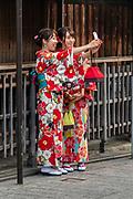 Kimono clad women capture a selfie photo in Gion district, Kyoto, Japan.