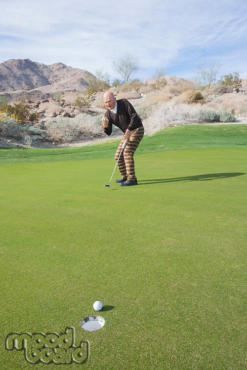 Full length of senior male golfer celebrating sinking putt at golf course