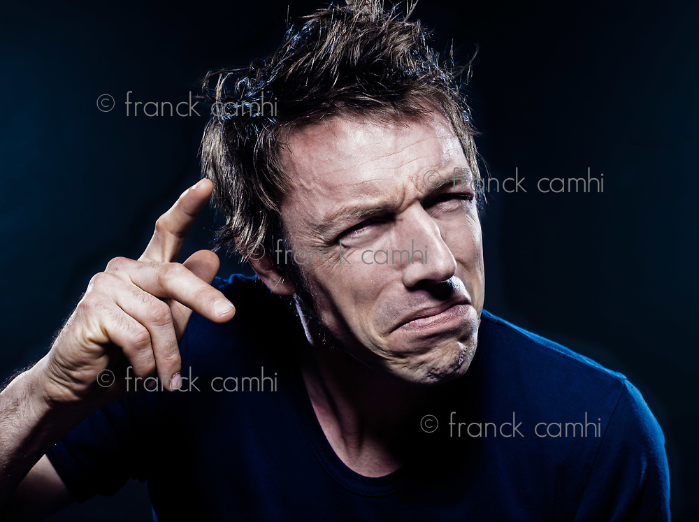 studio portrait on black background of a funny expressive caucasian man pucker foolish crazy