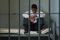 Prisoner sitting in his prison cell