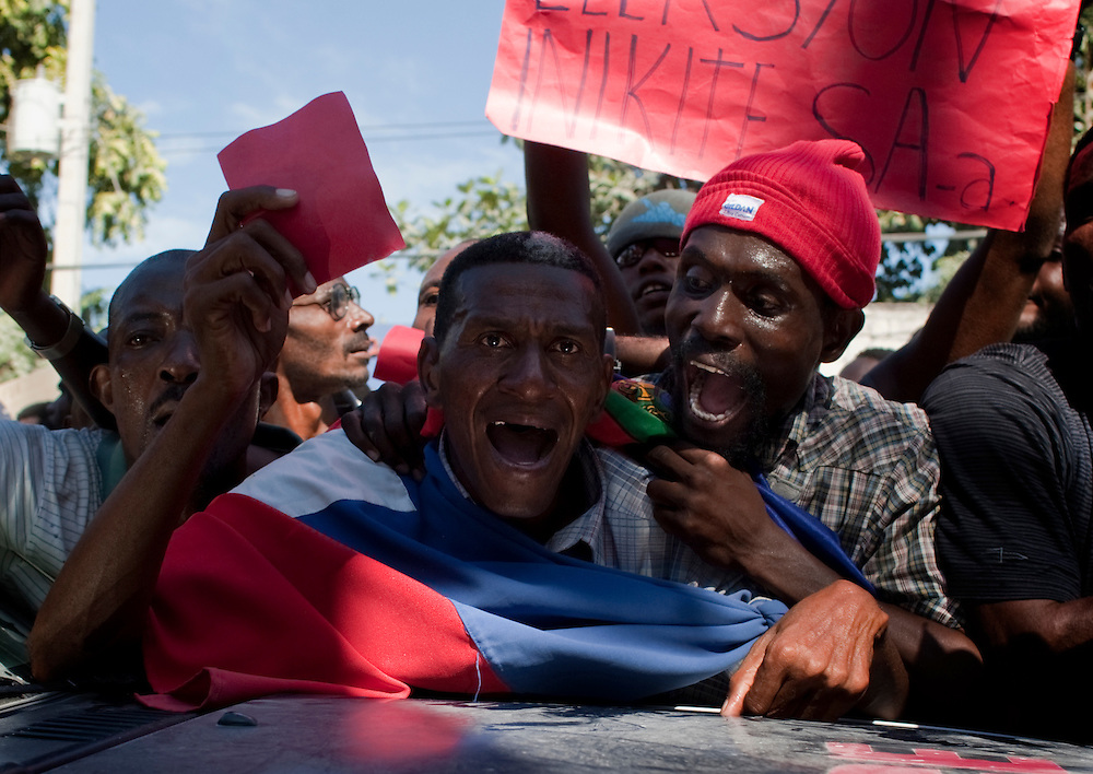 People shout slogans against president, Rene Preval, during a demostration outside police station.  Haiti elections, Thursday, Dec. 2, 2010.