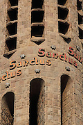 """""""Sanctus"""" repeated nine times in each bell tower of the temple, Passion façade, La Sagrada Familia, Antoni Gaudi, from 1883 to his death in 1926, still incomplete, Barcelona, Spain. The inscriptions use different colours: yellow when dedicated to God father, red when dedicated to God son and orange colour when dedicated to the Holy Spirit. Picture by Manuel Cohen"""