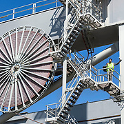 Nederland Zuid-Holland Rotterdam  27-08-2009 20090827 Foto: David Rozing .Serie over logistieke sector..ECT Delta terminal in de haven van Rotterdam. .Een kraanmachinist poseert op een van de reusachtige kranen. .ECT,European Container Terminals, at the Port of Rotterdam. Europe's biggest and most advanced container terminal operator, handling close to three- quarters of all containers passing through the Port of Rotterdam. ECT is a member of the Hutchison Port Holdings group (HPH), the world's biggest container stevedore with terminals on every Continent. At the ECT Delta Terminal unmanned, automated guided vehicles - so-called AGVs - transport the containers between ship and stack. In the stack, unmanned automated stacking cranes (ASCs) ensure that the containers are always stacked in the correct place. Thanks to the water depth ans its strategic location, many shipping lines have chosen the ECT delta Terminal as both their first and last European port of call. Terminal operations are highly automated. Consequently, the ECT Delta Terminal is exceptionally well suited to discharging and loading large volumes. ECT Delta Terminal offers an unequalled water depth. Rail Facilities.The ECT Delta Terminal has it own state-of-the-art rail facilities..Holland, The Netherlands, dutch, Pays Bas, Europe .Foto: David Rozing