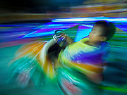 """07 MARCH 2015 - NAKHON CHAI SI, NAKHON PATHOM, THAILAND: A time exposure of a child on a merry-go-round on the midway at the Wat Bang Phra tattoo festival. Wat Bang Phra is the best known """"Sak Yant"""" tattoo temple in Thailand. It's located in Nakhon Pathom province, about 40 miles from Bangkok. The tattoos are given with hollow stainless steel needles and are thought to possess magical powers of protection. The tattoos, which are given by Buddhist monks, are popular with soldiers, policeman and gangsters, people who generally live in harm's way. The tattoo must be activated to remain powerful and the annual Wai Khru Ceremony (tattoo festival) at the temple draws thousands of devotees who come to the temple to activate or renew the tattoos. People go into trance like states and then assume the personality of their tattoo, so people with tiger tattoos assume the personality of a tiger, people with monkey tattoos take on the personality of a monkey and so on. In recent years the tattoo festival has become popular with tourists who make the trip to Nakorn Pathom province to see a side of """"exotic"""" Thailand.   PHOTO BY JACK KURTZ"""