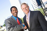 Portrait of two businessmen shaking hands, outdoors