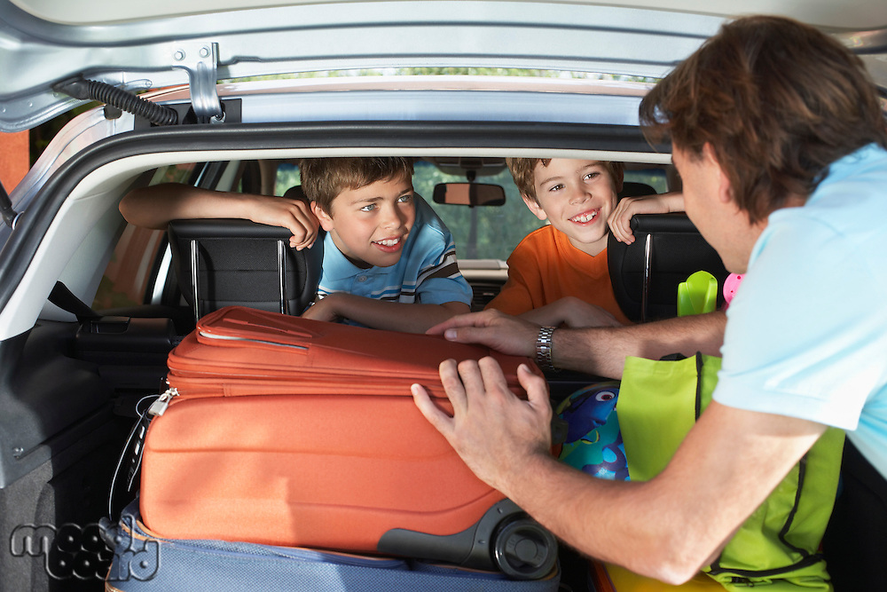 Father talking to boys (6-11) sitting in loaded car