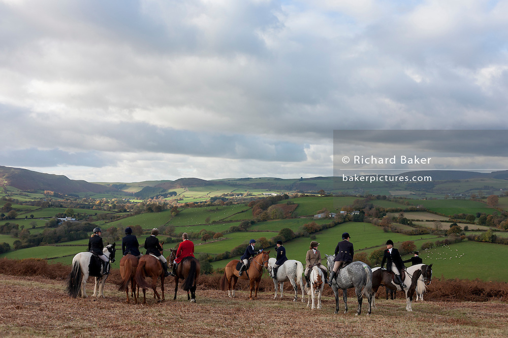 Members of a local hunt stop to admire the view with their horses overlooking the Welsh/English border between Gladestry and Kington.