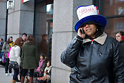 """October 16, 2010 - Michelle Jordan, a high school administrator from Dorchester, uses the phone while waiting to enter a campaign rally to reelect Governor Deval Patrick held at Hynes Convention Center on Saturday in Boston. Jordan said she had been in line since 6:45 a.m. for the event, which featured an appearance by President Barack Obama. She said of Obama, """" He's doing the best he can with what he was dealt with."""" After the event Jordan said, """"He is so real. Everything he said was so true."""" Photo by Lathan Goumas."""
