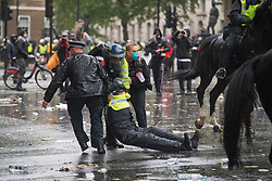 © Licensed to London News Pictures. 06/06/2020. London, UK. A mounted police officer is carried away by police colleges and a protester after falling off her horse during a Black Lives Matter demonstration in Westminster, London, over the killing of African American George Floyd. The death of George Floyd, who died after being restrained by a police officer In Minneapolis, Minnesota, caused widespread rioting and looting across the USA. Photo credit: Ben Cawthra/LNP