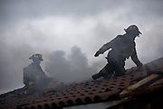 Fire fighters remove shingles from the roof as multiple fire departments, including Milpitas Fire Department, Spring Valley Fire Department, and Cal Fire, work to contain and extinguish a structure fire at the 3000 block of Calaveras Road near Spring Valley Golf Course in Milpitas, California, on February 10, 2014. (Stan Olszewski/SOSKIphoto)
