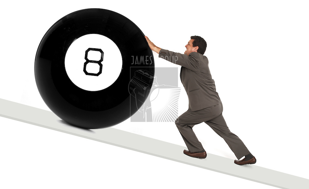 man in a business suit pushing a giant eight ball up a sloping ramp isolated on a white background
