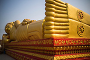 09 MARCH 2013 - VIENTIANE, LAOS:  A new reclining Buddha statue on the grounds of Pha That Luang in Vientianne, Laos. It is the most important Buddhist site in Laos and is the country's national symbol. It's likeness is on currency. It's said to date back to the 3rd century BC, but archeological and historic records indicate that construction on the site started in 1566. A piece of the Buddha's breast bone is thought to be in the stupa.  PHOTO BY JACK KURTZ