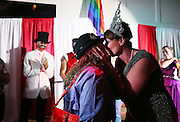 Debbie Murphy, center, kisses her wife Kimberly Carter, right, after Carter won the title of Shoals Pridefest Queen on Saturday at the Circus Masquerade. Carter will be featured in next year's Shoals Pridefest along with King Dwight Cox.