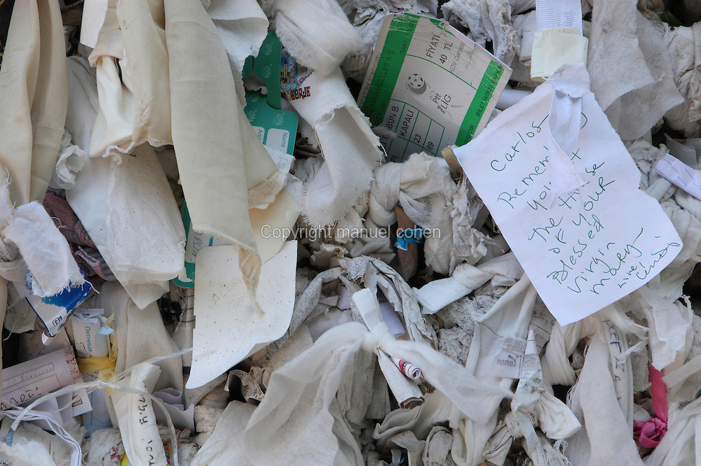 Scraps of paper and fabric with written wishes attached to the Wishing Wall at the House of the Virgin Mary on Bulbul Hill, 9km from Ephesus, Izmir, Turkey. Pilgrims, who believe the wall to be miraculous, attach their wishes to the wall. This is the place where Mary may have spent her last days. She may have come to the area with St John, who spent several years in the area spreading Christianity. The house of the Virgin Mary is typically Roman, made of stones. In the 4th century AD, a church, combining her house and grave, was built. Today, only the central part and a room on the right of the altar are open to visitors. Ephesus was an ancient Greek city founded in the 10th century BC, and later a major Roman city, on the Ionian coast near present day Selcuk. Picture by Manuel Cohen