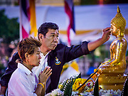 01 JANUARY 2019 - BANGKOK, THAILAND:   A man applies gold leaf to a statue of the Buddha at the New Year's merit making ceremony on the plaza in front of City Hall in Bangkok. City Hall traditionally hosts one of the largest New Year merit making ceremonies in Thailand. This year about 160 monks participated in the event.   PHOTO BY JACK KURTZ