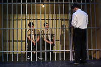 """Jonathan Buttrick PFC Louden Downey and Josh Testa Lance CPL Harold W. Dawson sit in their cell as Lt. Daniel Kaffee steps in for an interrogation during dress rehearsal for """"A Few Good Men"""" at Gilford High School Monday afternoon.  (Karen Bobotas/for the Laconia Daily Sun)"""