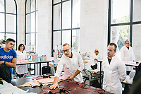 """ROME, ITALY - 15 OCTOBER 2018: Cristian (center), a leather artisan working for FENDI, explains the leather bags production process to students during the LVMH Journées Particulières exhibition at the Fendi headquarters in Rome, Italy, on October 15th 2018.<br /> <br /> The LVMH Journées Particulières is is a series of exhibitions that show the creations and history of the LVMH fashion houses. The driving theme behind the Journées Particulières is to allow the general public to discover the inner workings of the Houses which are part of the LVMH heritage.The LVMH Journées Particulières exhibition by fashion house FENDI takes place at their headquarters at the Palazzo della Civiltà Italiana, also called the """"Colosseo Quadrato"""" (Square Colosseum),  an outstanding jewel of the 20th century Roman architecture."""
