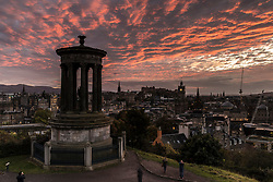 A stunning sunset over the city of Edinburgh looking from Calton Hill toward the Castle as strong winds and heavy rain is predicted for the following morning.