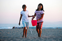 21 June 2008:  Two young girls use teamwork to help eachother carry a bucket of water from the pacific ocean to the fire pits in Huntington Beach, CA.