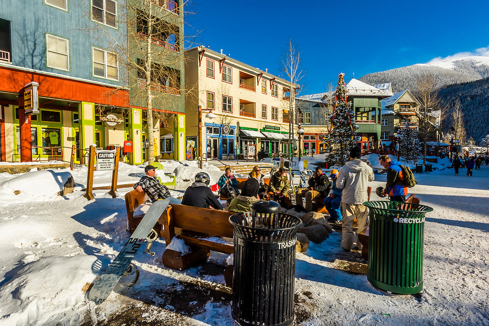 Skiers enjoy apres ski around an outdoor firepit, River Run Village, Keystone Resort, Colorado USA.