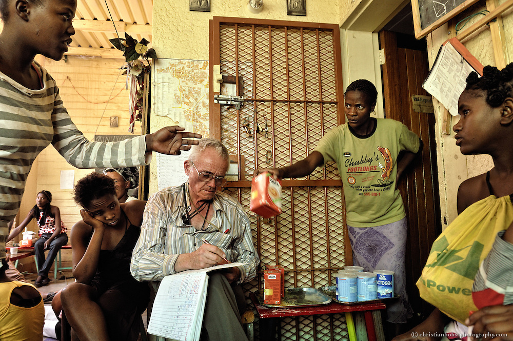 (2008) At his daycare facility, Father Hermann hands out milk powder to prevent small children from contracting HIV by their mothers from breastfeeding. In 2008, when this photo was taken, sex workers who registered with Hermann received a ration of food and second-hand clothing once per week. The bookkeeping of Father Hermann was always meticuluous. He knew exactly who got what and when.