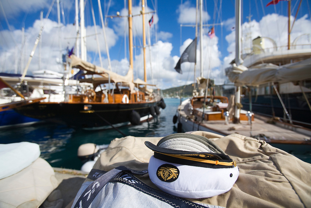 A traditional captains hat is left on top of a pile of sails at the 2008 Antigua Classic Yacht Regatta .  The yachts in the background are Ashanti vii and the other is unidentified. This race is one of the worlds most prestigious traditional yacht races. It takes place annually off the costa of Antigua in the British West Indies.
