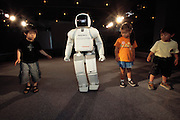 "ASIMO (Advanced Step in Innovative Mobility), is the newest addition to the Honda Humanoid Robot family. It is on display daily at Suzuka City Circuit, where young and old converge to watch racing, ride amusement park rides, and also watch this child-sized robot introduced by a beauty queen walk, wave, and dance four times daily. The press literature for ASIMO states ""By helping people, and becoming their partners, Honda robots are opening the door to the 21st Century."" Honda R&D expects that ""ASIMO will help improve life in human society.""."