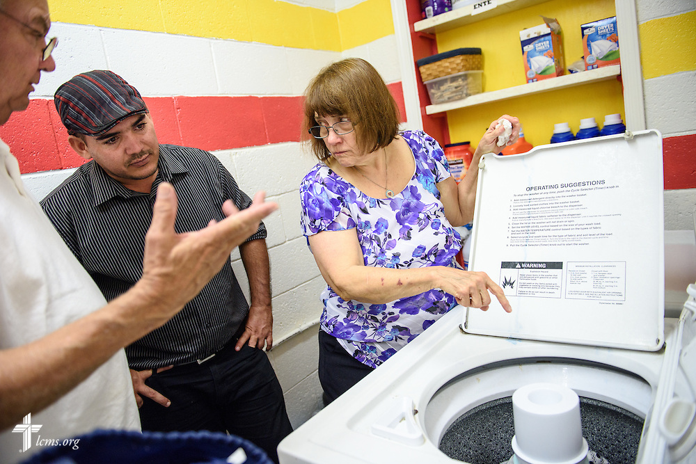 Jeanette Heimer and her husband, the Rev. Karl Heimer, pastor of San Pablo Lutheran Church and president of Ysleta Lutheran Mission Human Care, shows Ahmed Cespedes, a new Cuban immigrant, how to use the laundry machine on Friday, May 20, 2016, at  in the dormitory at YLM in El Paso, Texas. LCMS Communications/Erik M. Lunsford
