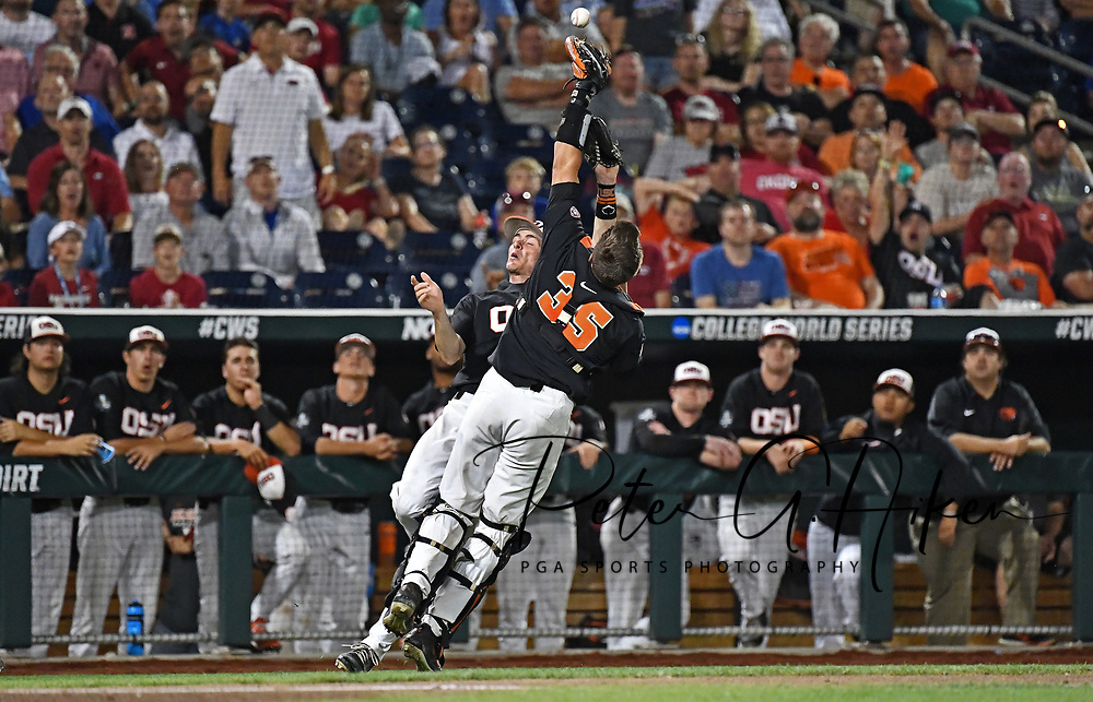 Infielder Michael Gretler #10 of the Oregon State Beavers and catcher Adley Rutschman #35 collide attempting to catch a foul ball in the ninth inning against the Arkansas Razorbacks during game one of the College World Series Championship Series at TD Ameritrade Park in Omaha, Nebraska.