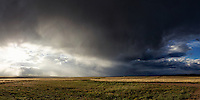 Panoramic of the Wet Mountain Valley near Westcliffe, Colorado as the sun sets through afternoon rain showers