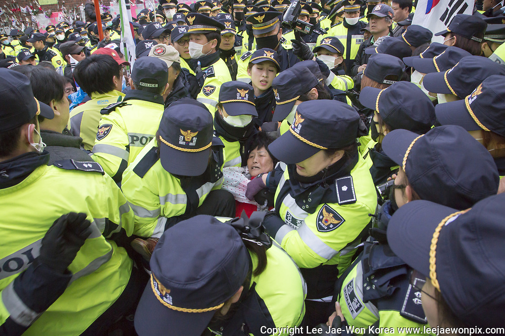 Policemen carry a supporter (C) of former South Korean President Park Geun-Hye as her supporters hold a sit-in in front of her home in an attempt to block her before she leaves to go to the Seoul Central District Court in Seoul, South Korea, Mar 30, 2017. The court held a hearing on Thursday to decide whether to issue an arrest warrant for her over corruption allegations that fired her. South Korea's prosecutors filed the request on Monday to detain Park Geun-Hye on charges of abuse of authority, coercion, bribery and leaking government secrets, citing the graveness of the alleged crimes and the possibility of the destruction of evidence, local media reported. Photo by Lee Jae-Won (SOUTH KOREA) www.leejaewonpix.com