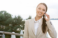 Portrait of happy businesswoman answering cell phone outdoors