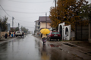 A woman with a yellow umbrella is walking the main road in Marginenii de Jos. The village has about 3400 inhabitants. The majority population are Roma with 2700 citizens and 700 non Roma.