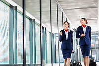 Portrait of attractive flight attendants walking with their suitcase in airport