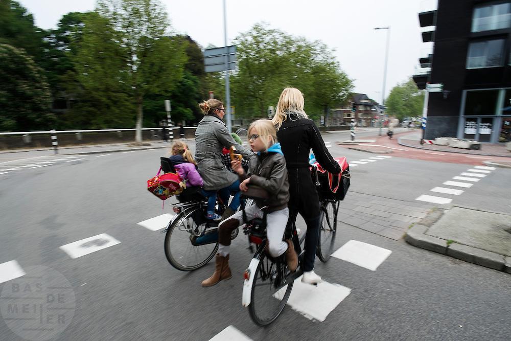 Een meisje zit achterstevoren achterop de fiets te eten.<br /> <br /> A girl is sitting backwards at the back seat of a bike eating a bread.