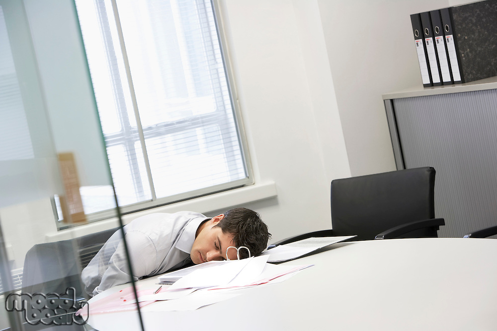 Businessman asleep at desk in office by scattered files