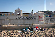Litter and graffiti on the beach of Lisbon's Praca do Commercio.