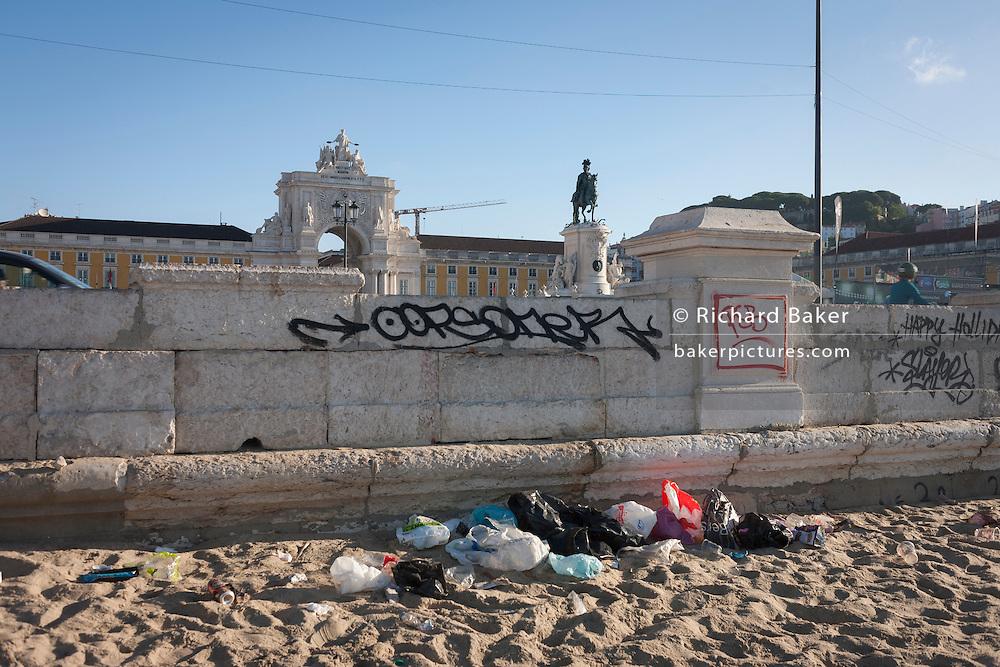 Litter and graffiti on the beach of Lisbon's Praca do Commercio.