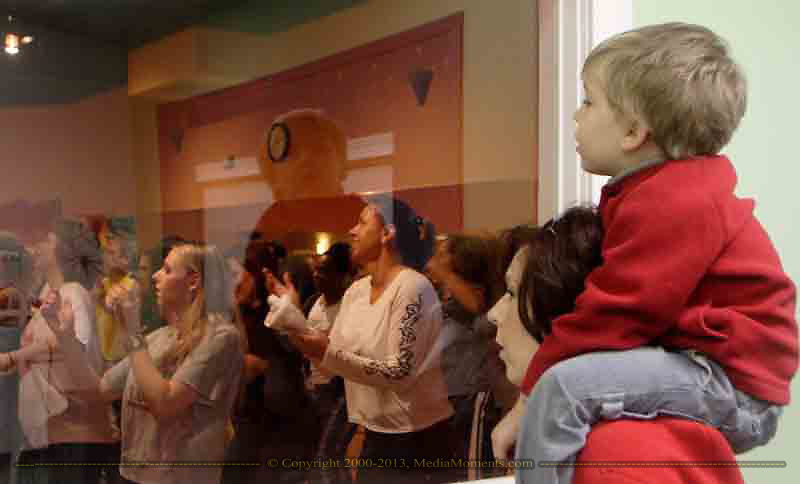Connor Lowman, 3, from Huber Heights, sits on his mother Kris' shoulder and takes a peek at the dancers during the grand opening of Studio Zumba in Vandalia, Sunday, January 28, 2007.  They're watching from the area that will be used for daycare during classes.