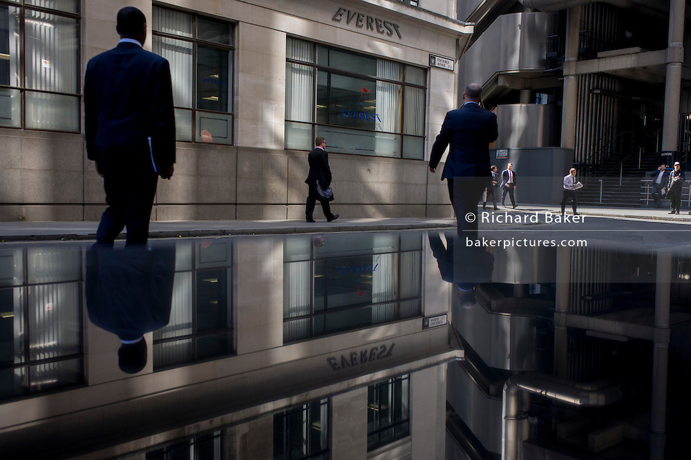 Reflections of workers in Lime Street, the insurance business district of the City of London.