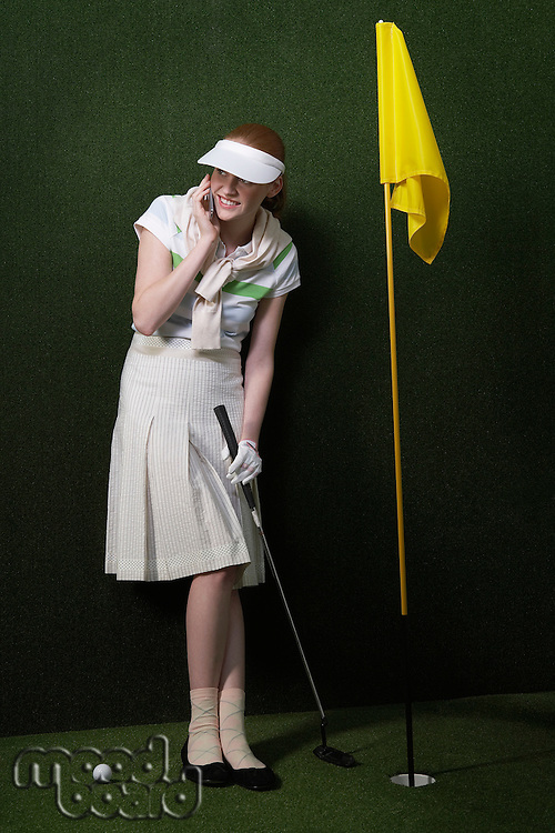 Woman in visor holding golf club by flag in hole