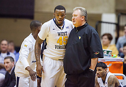 Nov 28, 2016; Morgantown, WV, USA; West Virginia Mountaineers head coach Bob Huggins talks with West Virginia Mountaineers forward Elijah Macon (45) on the bench during the first half against the Manhattan Jaspers at WVU Coliseum. Mandatory Credit: Ben Queen-USA TODAY Sports