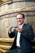 Nicolas Soergel, managing director of Chinriu Honten Ltd., samples an umeboshi products in front of a 140-year-old pickling barrel at his company's store in Odawara, Kanagawa Prefecture, Japan on 30 May 2010. Photographer: Robert Gilhooly