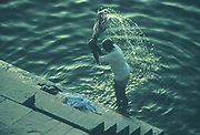 A man washes clothes in the Ganges river, Varanasi, India 1997.
