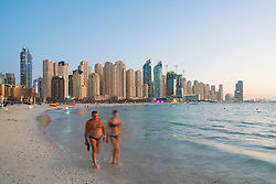 Evening view of beach and skyline of high-rise apartment blocks at JBR Jumeirah Beach Residences in Dubai UAE