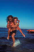 A man giving a girl a piggy back ride in the sea, Ibiza 2000