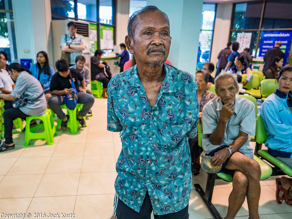 15 DECEMBER 2016 - PRACHINBURI, THAILAND: A man waits for his cash disbursements in a government credit union in Prachinburi, Thailand. The Thai government said people who earn 30,000 Baht (about $857 US) or less per year are entitled to a 3,000 Baht cash payment (about $85.7 US) and those who earn 30,000 Baht to 100,000 Baht (about $2,857 US) per year are entitled to a 1,500 Baht (about $42.8 US) cash payment. The plan is meant to help low income people, especially the rural poor. Government banks in rural areas offering the disbursement have been crowded with people seeking their payments this week.      PHOTO BY JACK KURTZ   Social Safety Net