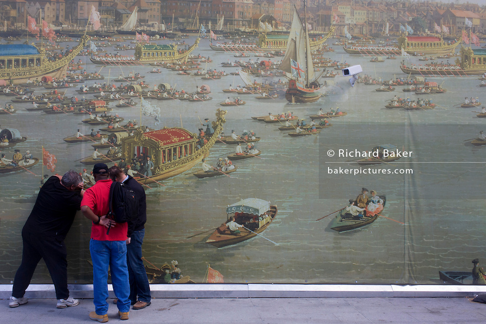 CCTV camera watches men peeling the background of Canaletto's 18th century painting of the Lord Mayor's Show regatta at London Bridge railway station. The  30-metre-long work of art is positioned on a temporary wall at the recently-refurbished station entrance. The picture is a reproduction of Canaletto's The Thames on Lord Mayor's Day, Reproduced at this scale commuters and tourists are be able to admire the detail of the famous painting depicting the bustling activity of the Lord Mayor's Show river procession as seen from Bankside before 1752.