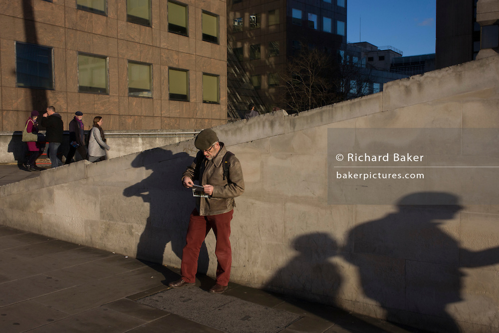A man stops to consult a map on the south side of London Bridge in Southwark, central London