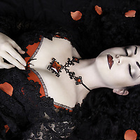 Female lying down asleep or dead with rose petals